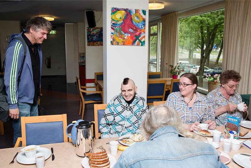 Gezamenlijke lunch, georganiseerd door de bewoners. Meindert (links) probeert de mensen als touwtjes aan elkaar te knopen opdat er iets van een social vangnet ontstaat. Foto: Peter de Krom