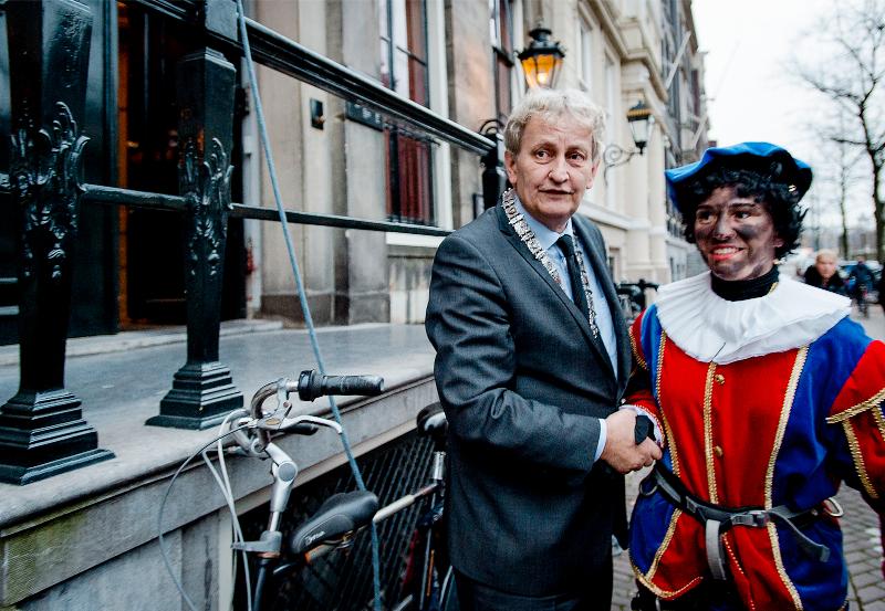 Burgemeester Van Der Laan begroet de Roetpiet. Foto: Robin van Lonkhuijsen/ANP