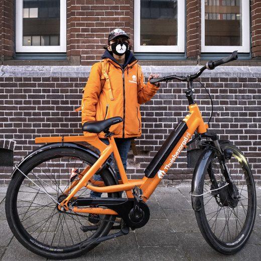 Foto van een fietskoerier van Thuisbezorgd